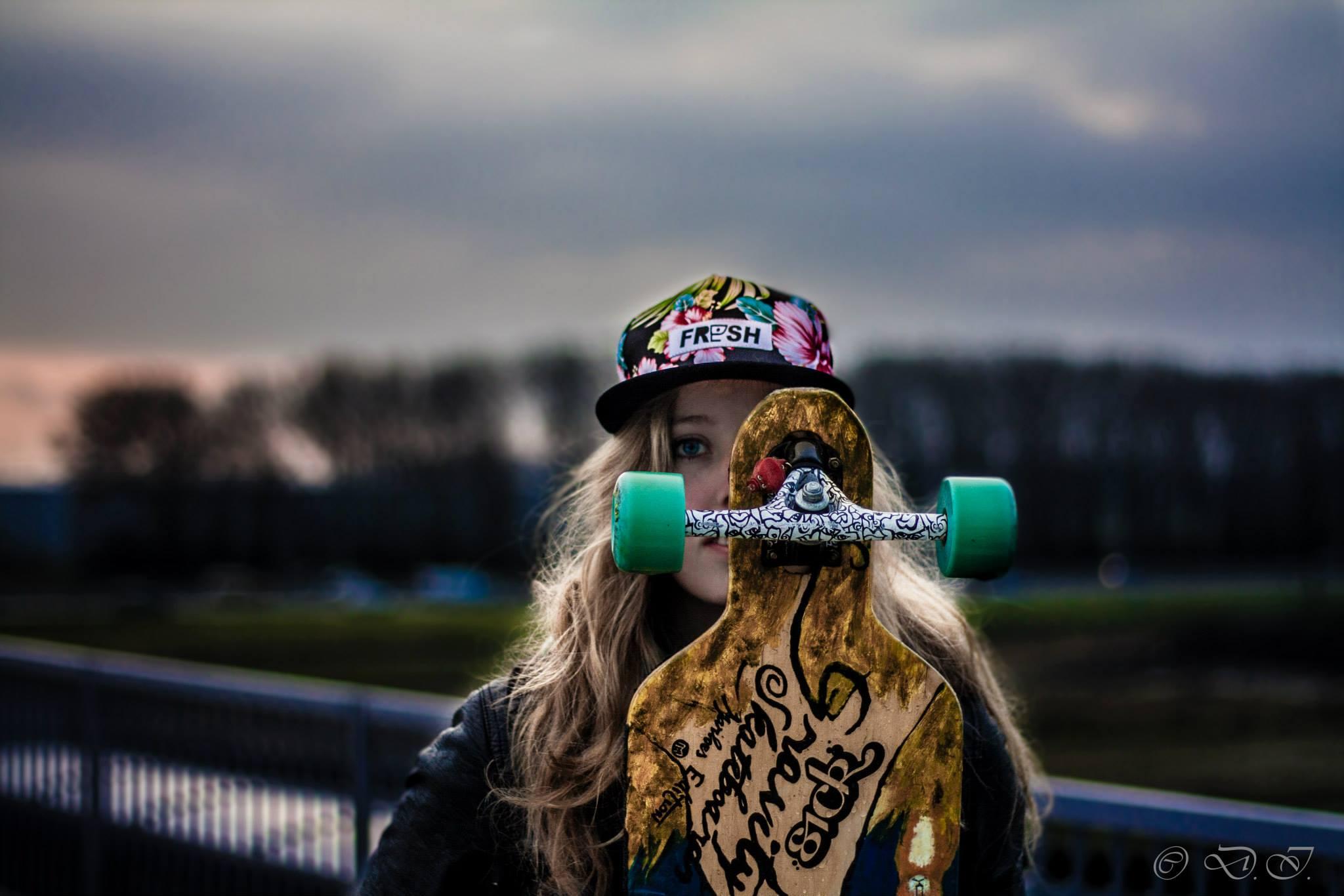 meisje met longboard voor haar gezicht