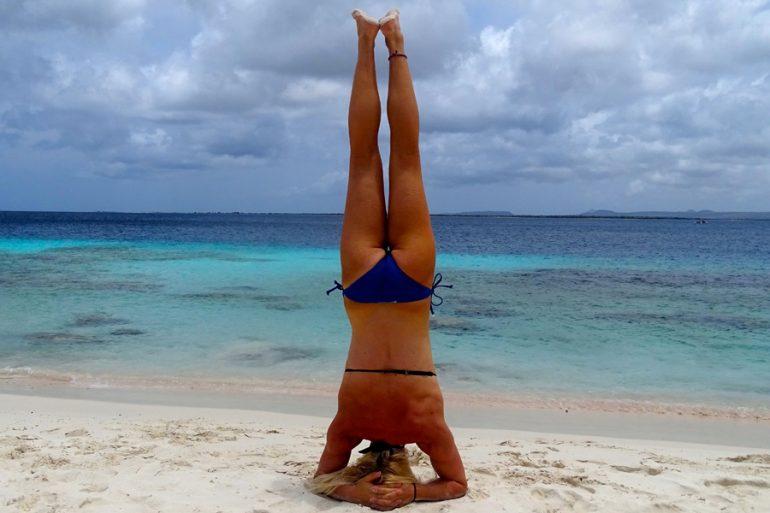 Meisje op de kop op het strand