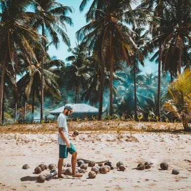 man met kokosnoot op het strand