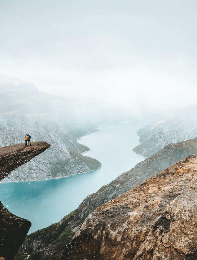reisblogger stel bovenop de trolltunga rotsformatie met uitzicht over de fjorden