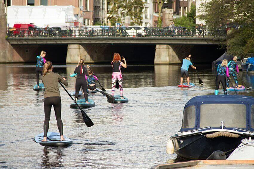 Meiden op supboards op de Amsterdamse grachten